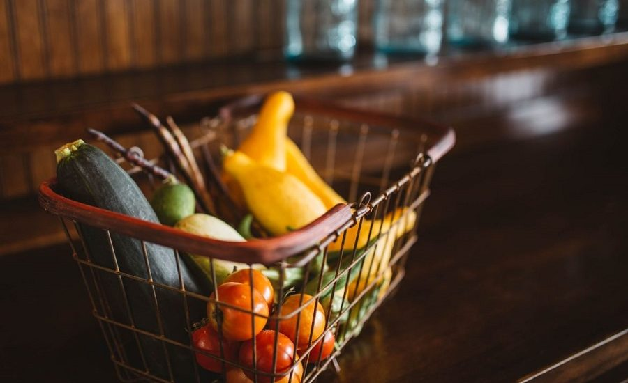 Basket of vegetables including tomatoes, zucchini and squash