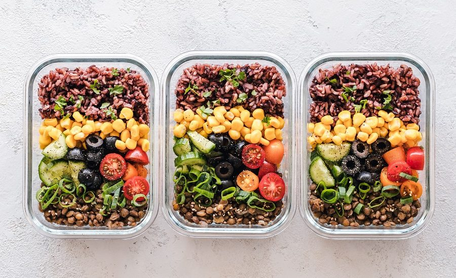 Three glass containers filled with lentils, rice, corn, olives, green onions, cucumbers and tomatoes