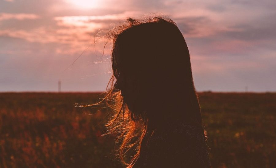 Girl standing in a cornfield during sunset