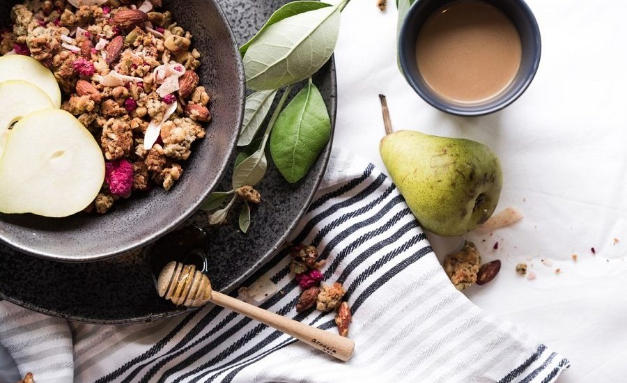 Granola with pears in a dark ceramic bowl with herbs and honey on a plate underneath it
