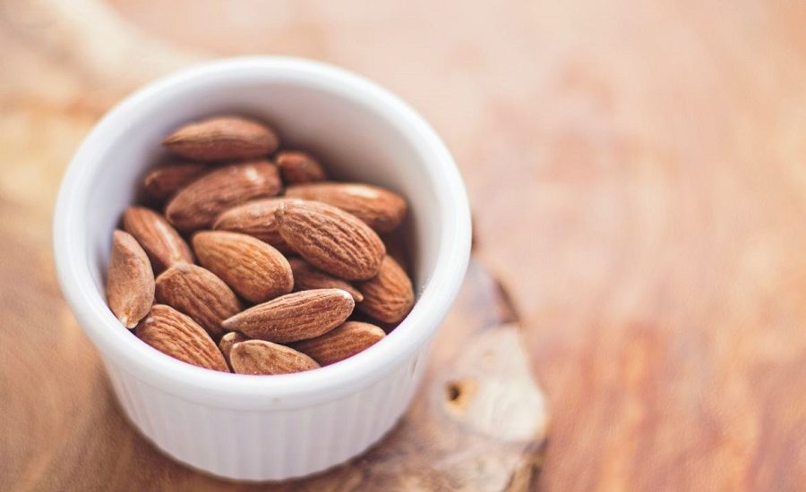 White ceramic bowl holding almonds on top of a wooden surface