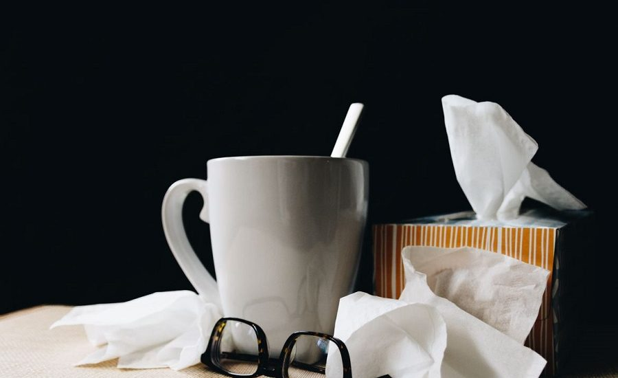 Ceramic mug surrounded by a tissue box, tissues and glasses