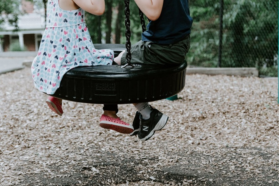 A boy and a girl on the tireswing