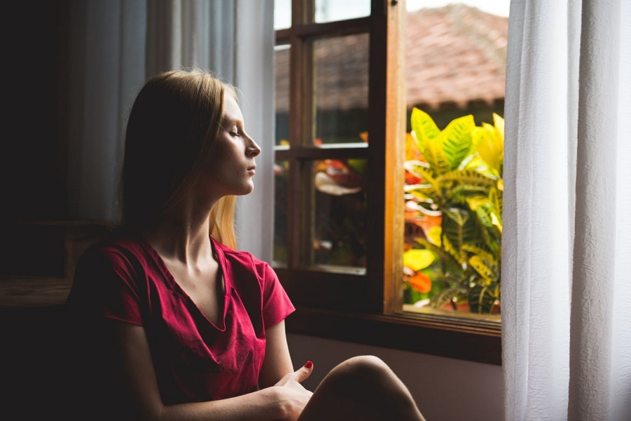 Woman sitting with her eyes closed, facing an open window