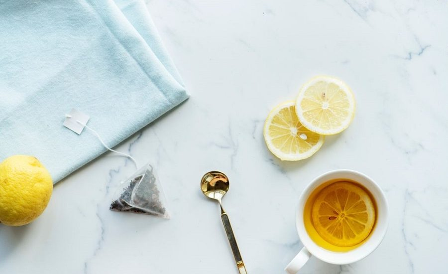 Tea in a white ceramic mug surrounded by a spoon, tea bag, and slices of lemon