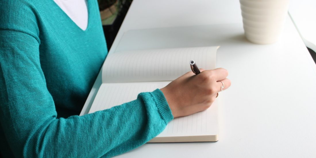 Woman in a teal blue sweater writing in a notepad