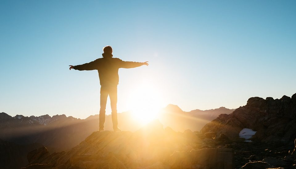 Man standing on top of a mountain as the sun rises with arms outstretched