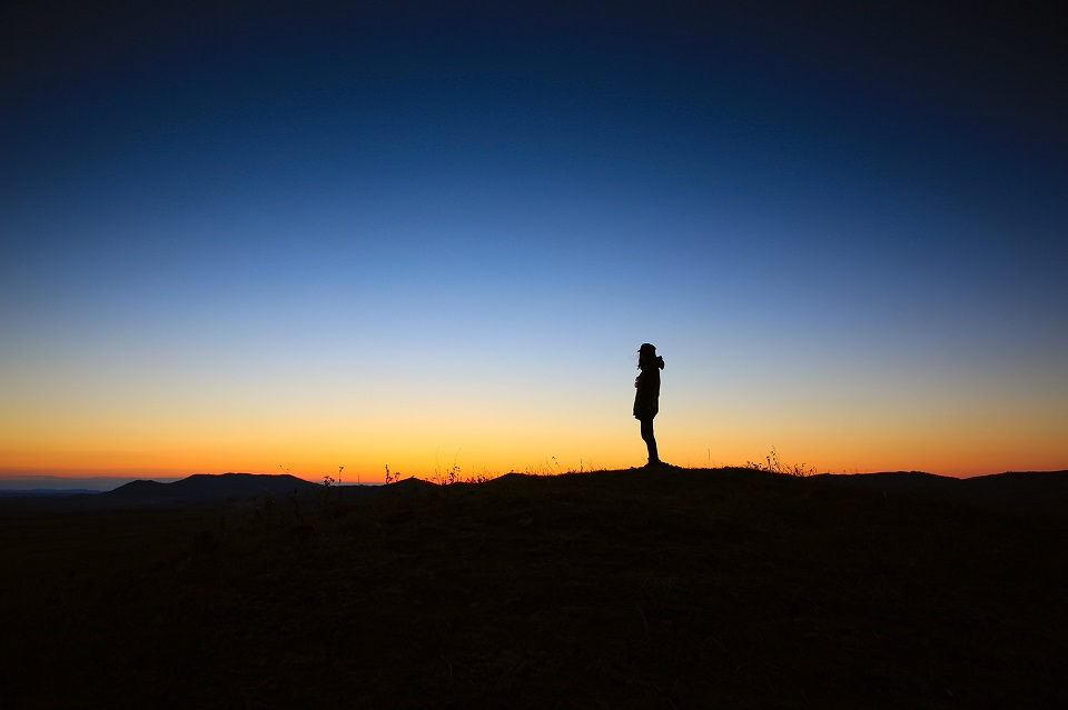Shadowy man standing in sunset